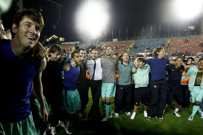 Barcelona players and coach Pep Guardiola, center, celebrate after the team was crowned Spanish champions for the third successive season with a 1-1 draw at Levante, clinching a 21st domestic title with two games to spare. (AP PHOTO)