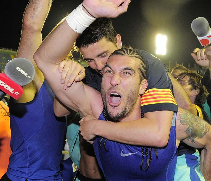 Barcelona forward David Villa and goalkeeper Jose Manuel Pinto celebrate after after the team was crowned Spanish champions for the third successive season with a 1-1 draw at Levante, clinching a 21st domestic title with two games to spare. (AFP PHOTO)