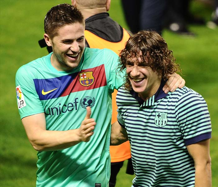 Barcelona captain Carles Puyol and Andreu Fontas celebrate after the team was crowned Spanish champions for the third successive season with a 1-1 draw at Levante, clinching a 21st domestic title with two games to spare. (AFP PHOTO)