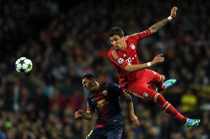 Barcelona's Brazilian defender Adriano (L) vies with Bayern Munich's Croatian striker Mario Mandzukic during the UEFA Champions League semi-final second leg football match between FC Barcelona and FC Bayern Munich at the Camp Nou on Wednesday, May 1, 2013.