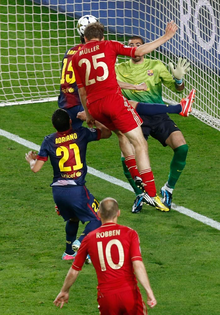 Bayern Munich's midfielder Thomas Mueller (C) heads the ball in the 76th minute to score the third goal of the eveing during the UEFA Champions League semi-final second leg match, ultimately giving his side a 7-0 aggregate win over Barcelona.