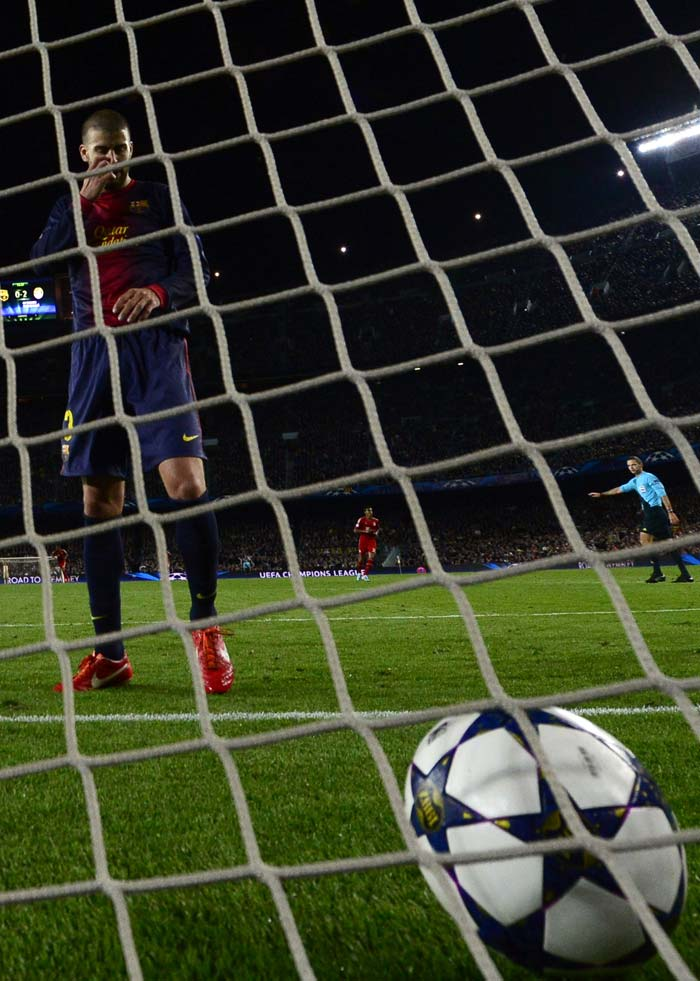 Barcelona's defender Gerard Pique (L) looks at the ball in the net after his own goal at 72nd minute took Bayern Munich closer to the Champions League final at the Camp Nou stadium in Barcelona.