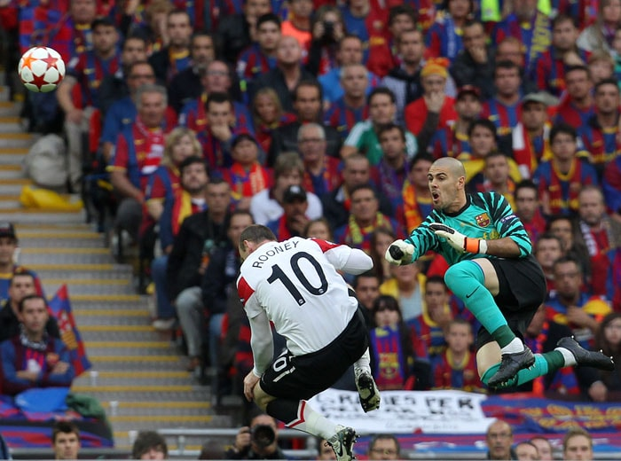 Barcelona's Spanish goalkeeper Victor Valdes (R) boxes the ball in front of Manchester United's English forward Wayne Rooney during the UEFA Champions League final at the Wembley stadium in London. (AFP PHOTO)