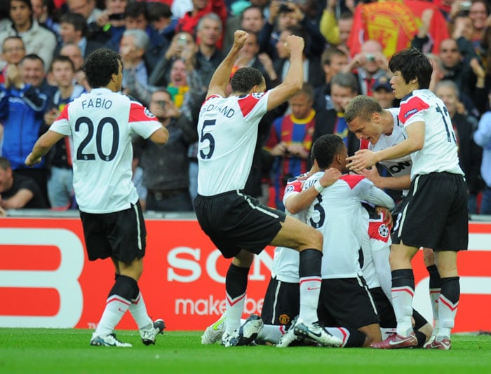 Manchester United's English forward Wayne Rooney (hidden) is congratulated by teammates after scoring a goal during the UEFA Champions League final against Barcelona at the Wembley stadium in London. (AFP PHOTO)