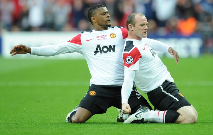 Manchester United's English forward Wayne Rooney (R) is congratulated by team-mate Patrice Evra (L) after scoring a goal during the UEFA Champions League final against Barcelona at the Wembley stadium in London. (AFP PHOTO)