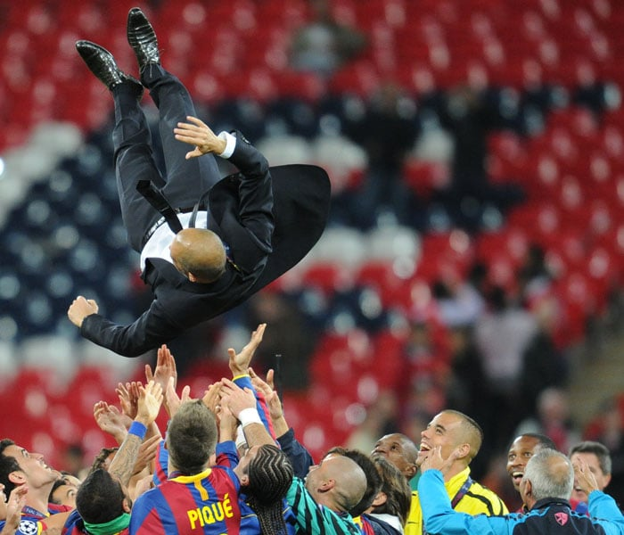 Barcelona's Spanish coach Josep Guardiola is flung in the air in celebration at the end of the UEFA Champions League final between Barcelona and Manchester United at the Wembley stadium in London. (AFP PHOTO)