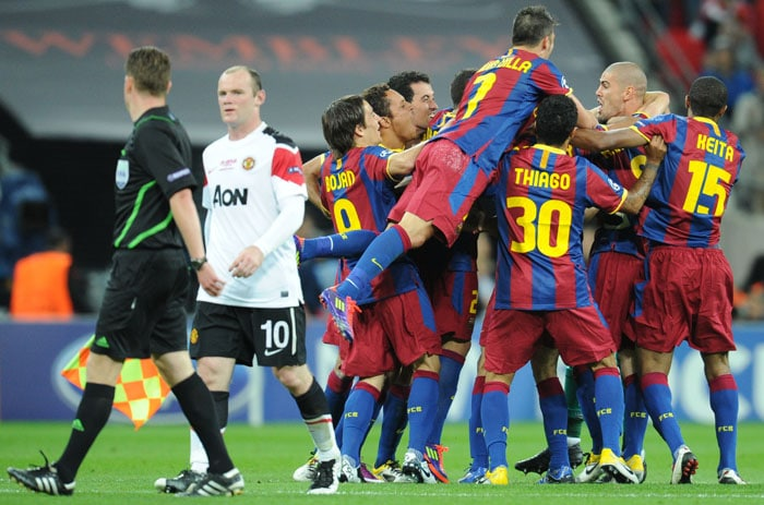 Barcelona's players celebrate next to Manchester United's English forward Wayne Rooney (2ndL) at the end of the UEFA Champions League final between Barcelona and Manchester United at the Wembley stadium in London. (AFP PHOTO)