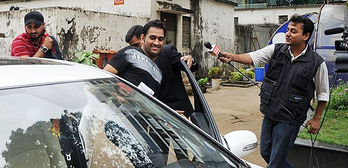 An Indian television journalist makes an attempt to interview cricketers Harbhajan Singh MS Dhoni as they leave the BCCI headquarters in Mumbai after an emergency session to discuss the players' refusal to sign the clause with WADA. (AFP Photo)
