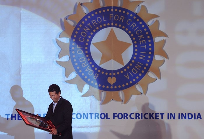 Sachin Tendulkar holds a commemorative plaque presented to him for scoring the highest number of Test runs at the BCCI annual award function in Mumbai. (AFP Photo)