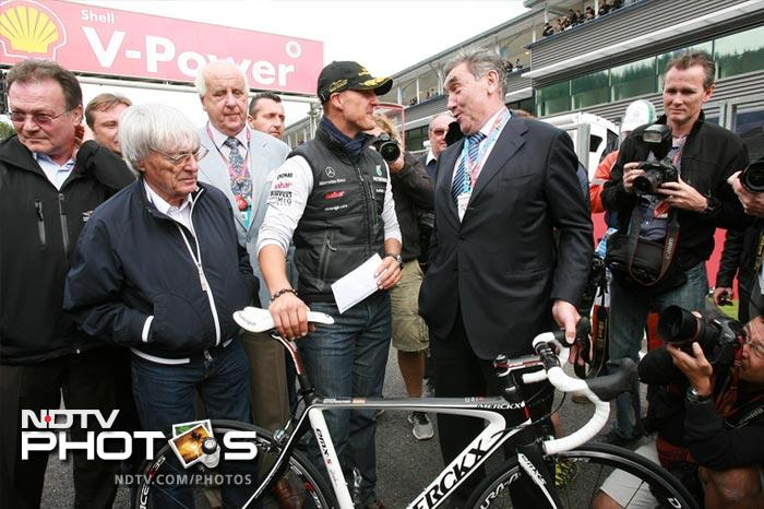 Formula 1 chief executive Bernie Ecclestone (2-L) and Michael Schumacher of Mercedes GP (C) meet with former cycling champion Eddy Merckx (R). Schumacher finished the race on the 5th position.