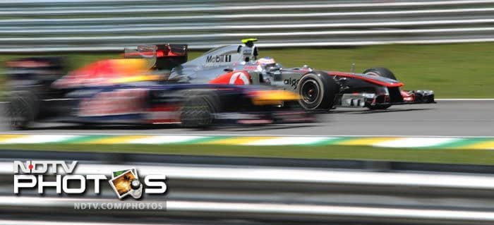 The McLaren of Lewis Hamilton powers past a Red Bull during the qualifying session.