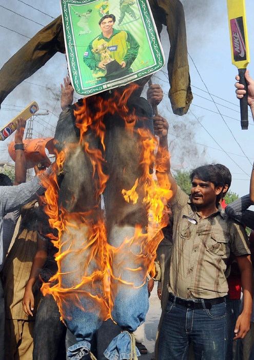 Pakistani cricket fans hold a burning effigy of national cricket team captain Salman Butt during a protest against a match fixing scandal, in Lahore. (AFP Photo)