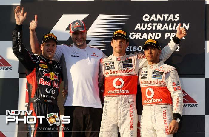 From left to right, Red Bull driver Sebastian Vettel (2nd place) of Germany, Chief Aerodynamicist for McLaren Racing, Doug McKiernan, McLaren driver Jenson Button (winner) and his team-mate Lewis Hamilton (3rd place) wave from the podium after the Australian Formula One Grand Prix at Albert Park.