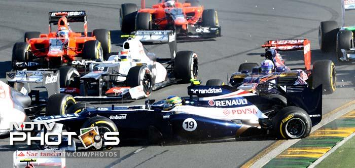 Williams-Renault driver Bruno Senna of Brazil (C) is caught in an incident at the first turn in Formula One's Australian Grand Prix in Melbourne.