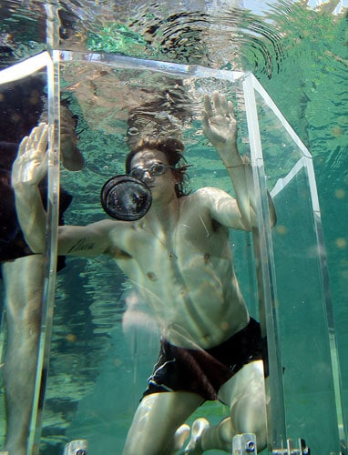 Australian cricketer Nathan Bracken (centre) dives in the 'Cage of Death' for an up-close experience with a crocodile at Crocosaurus Cove in Darwin.
