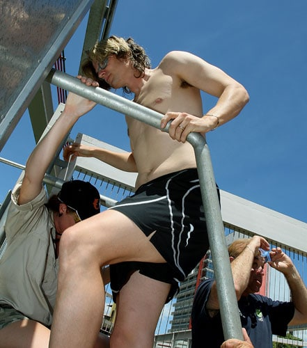 Australian cricketer Nathan Bracken (C) enters the 'Cage of Death' for an up-close experience with a crocodile at Crocosaurus Cove in Darwin. Bracken and Australian fielding coach Mike Young dived in the pen of 80-year-old crocodile Chopper at the tourist attraction in the centre of Darwin.