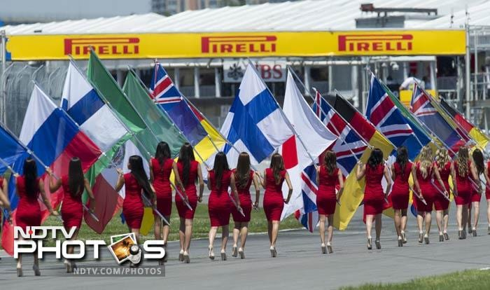 Flag-bearers make their way to the start line before the Canadian Formula One Grand Prix at the Circuit Gilles Villeneuve in Montreal. (AFP Photo)