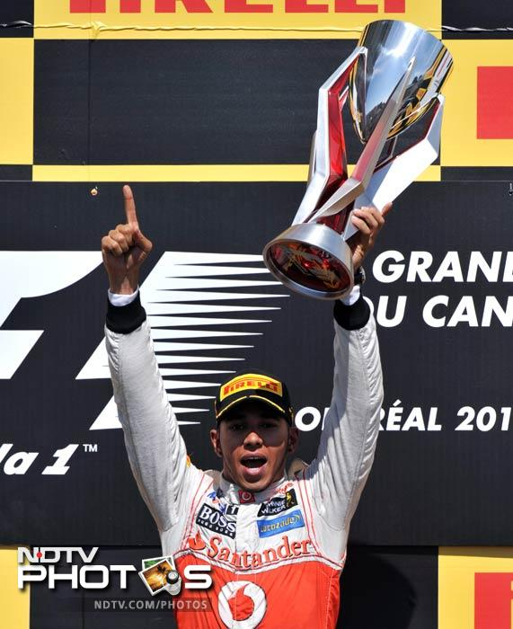 McLaren Mercedes driver Lewis Hamilton of Britain holds up the trophy after winning the Canadian Formula One Grand Prix at the Circuit Gilles Villeneuve in Montreal. (AFP Photo)