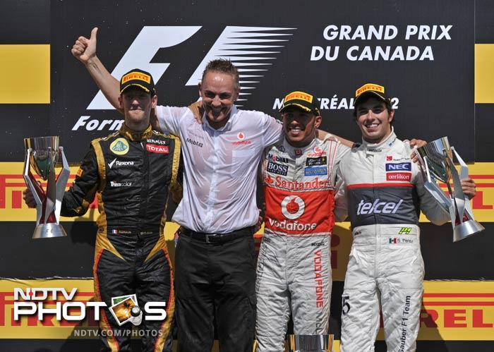 Second place finisher Lotus Renault GP driver Romain Grosjean of France, McLaren Team Principal Martin Whitmarsh, winner McLaren Mercedes driver Lewis Hamilton of Britain and third place finisher Sauber Ferrari driver Sergio Perez of Mexico celebrate after the Canadian Formula One Grand Prix at the Circuit Gilles Villeneuve in Montreal. (AFP Photo)