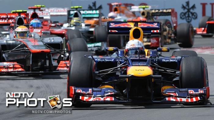 Cars fight for position behind Red Bull Racing driver Sebastian Vettel of Germany in the first lap of the Canadian Formula One Grand Prix at the Circuit Gilles Villeneuve in Montreal.