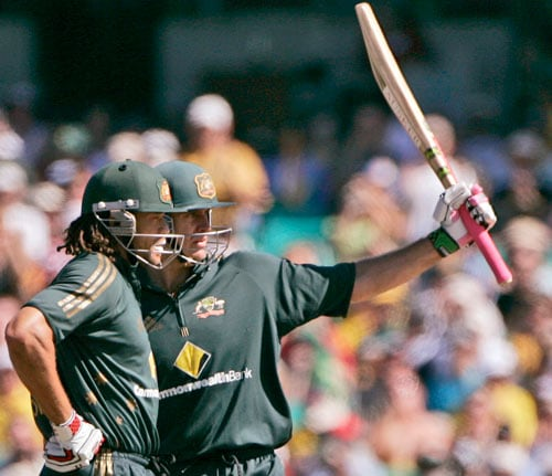 Matthew Hayden, right, raises his bat after making 50 runs against India as teammate Andrew Symonds stand alongside during the first final of their tri-nations one-day international series at the Sydney Cricket Ground on Sunday, March 2, 2008.