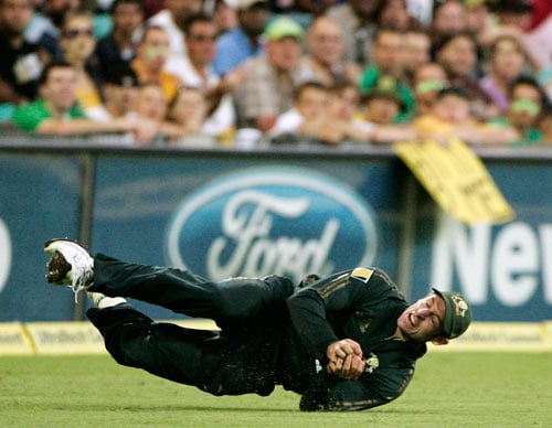Michael Hussey rolls on the ground after catching out India's Robin Uthappa during the first final of their tri-nations one-day international series at the Sydney Cricket Ground on Sunday, March 2, 2008. Australia made 239 in their innings.