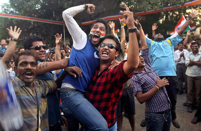 Indian cricket fans cheer for their team as they watch on a projection screen the World Cup cricket final match between India and Sri Lanka. (Photo courtesy: AP)