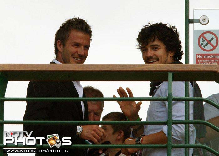 Beckham runs into British actor Orlando Bloom (R) during the 2010 Wimbledon Championships at the All England Lawn Tennis Club.