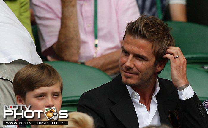 England football star David Beckham, along with with son Brooklyn, watches a match during the 2010 Wimbledon Championships at the All England Lawn Tennis Club.