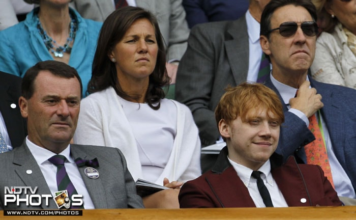 British actor Rupert Grint, who plays Ron Weasley in the Harry Potter movie series, sits with All England Lawn Tennis Club Chairman Philip Brook as they watch play on Centre Court at the All England Lawn Tennis Championships at Wimbledon. (AP Photo)