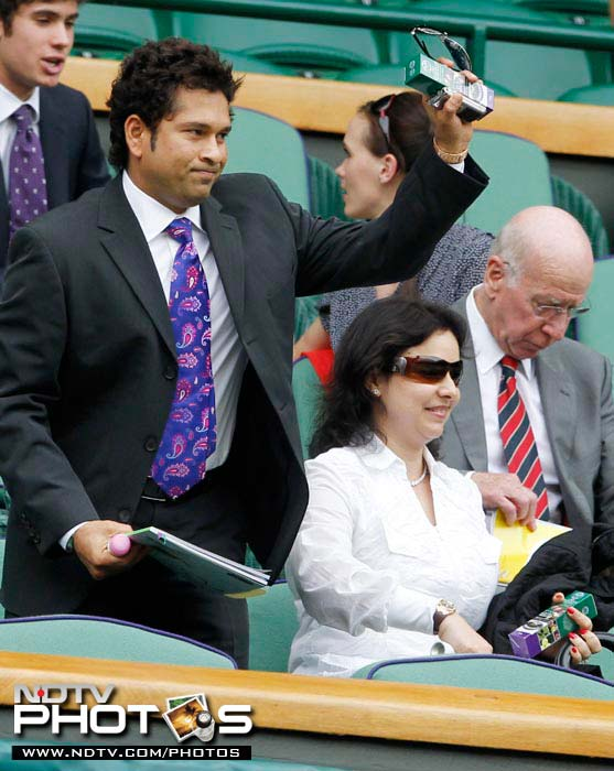Indian cricketer Sachin Tendulkar waves as he is introduced to the crowd on Centre Court at the All England Lawn Tennis Championships at Wimbledon 2010. He is accompanied by wife Anjali while Manchester United legend, Sir Bobby Charlton gets settled beside them.