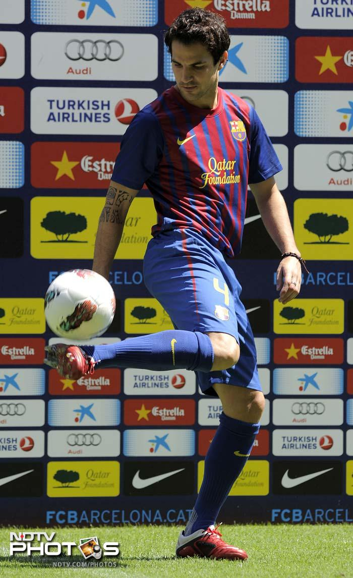 Fabregas plays with a ball during his official presentation at the Camp Nou's stadium in Barcelona.