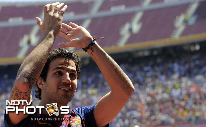 The 24-year-old mid-fielder applauds during his official presentation at the Camp Nou's stadium in Barcelona.