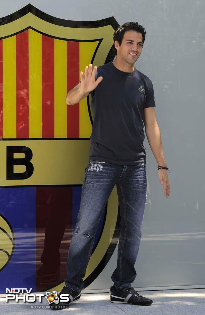Barcelona's new player Cesc Fabregas poses outside the Camp Nou's stadium in Barcelona.