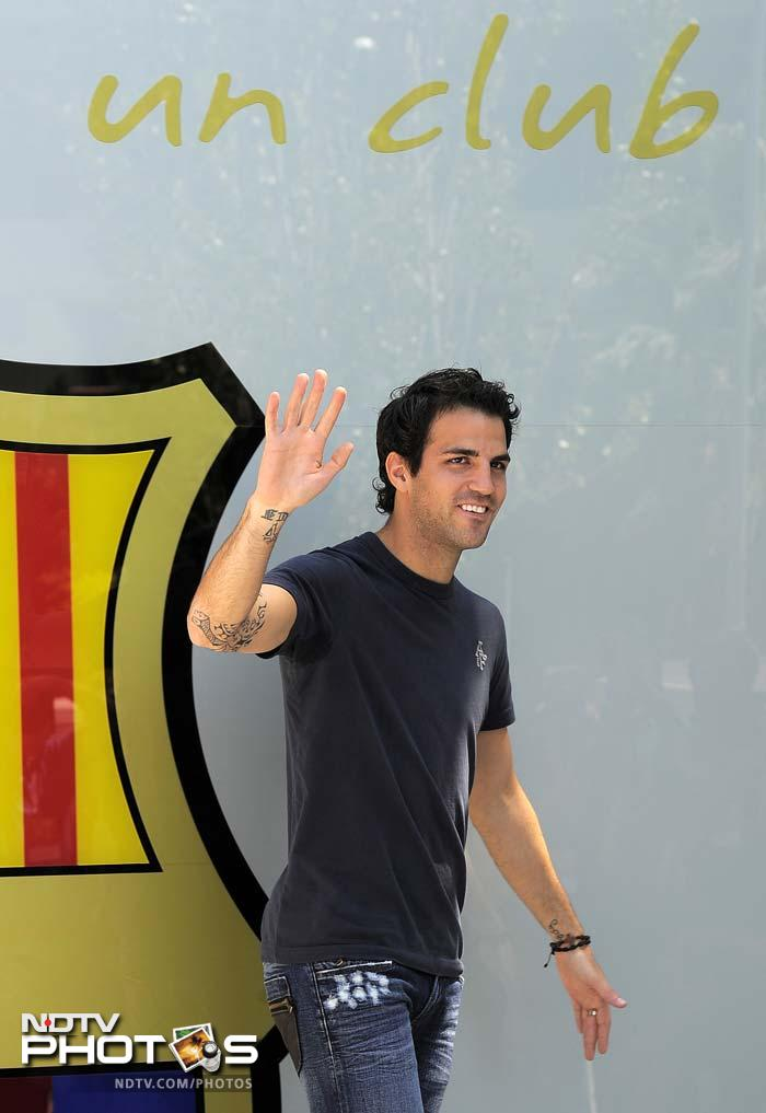 Barcelona's new player Cesc Fabregas waves to supporters outside the Camp Nou's stadium in Barcelona.