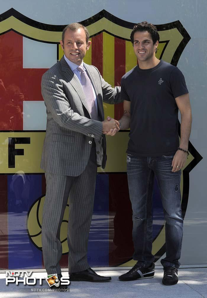 Fabregas shakes hands with Barcelona's president Sandro Rosell (L) outside the Camp Nou's stadium.