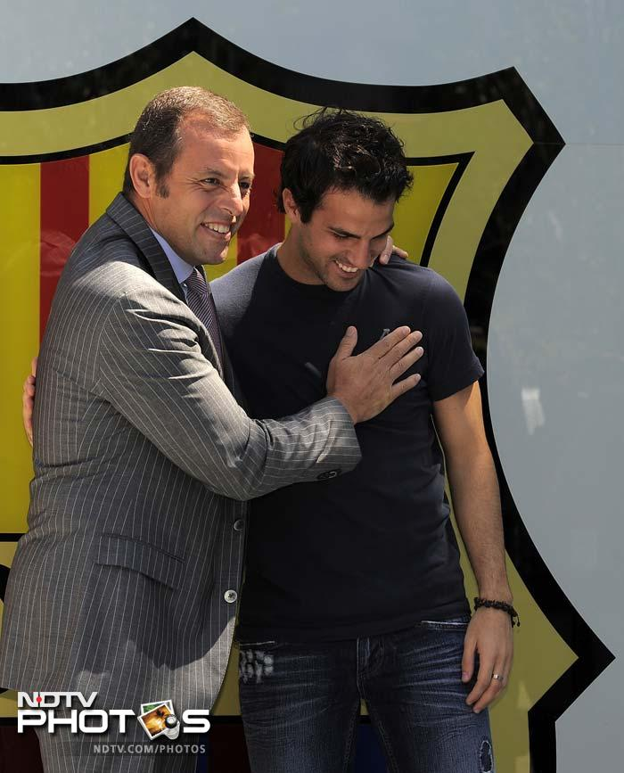 Barcelona's president Sandro Rosell (L) gestures with Fabregas by his side in front of the media and fans (unseen).