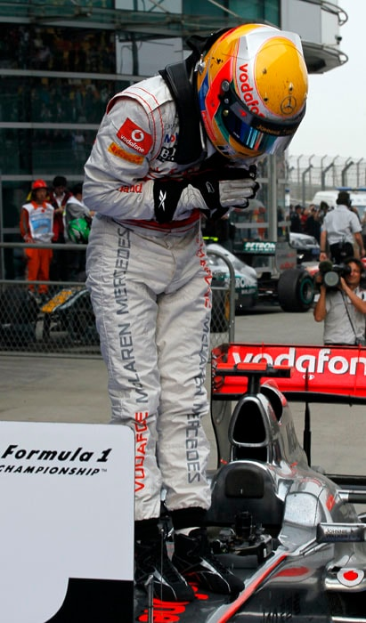 McLaren Formula One driver Lewis Hamilton of Britain bows to greet his camp after winning the Chinese Formula One Grand Prix in Shanghai, China. (AP Photo)