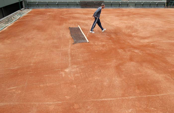 A maintenance worker cleans the ground on the Suzanne Lenglen court after setting the last layer of clay at the Roland Garros tennis stadium in Paris. (AFP Photo)