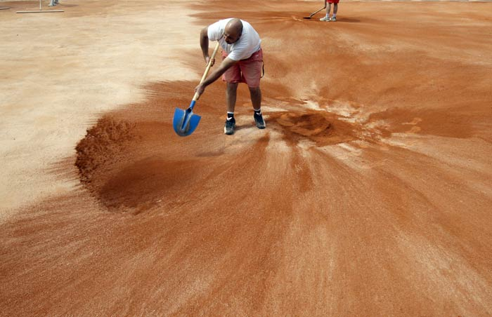 An employee puts the last layer of clay with a shovel on the Suzanne Lenglen court at the Roland Garros tennis stadium in Paris. (AFP Photo)