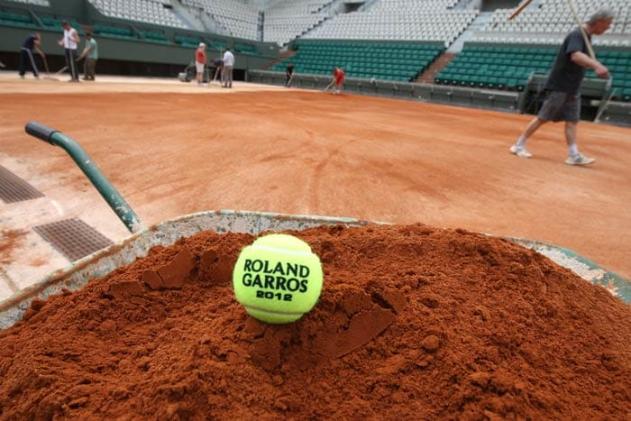 After the clay is spread, layers of crushed brick is spread on the court. (AFP Photo)