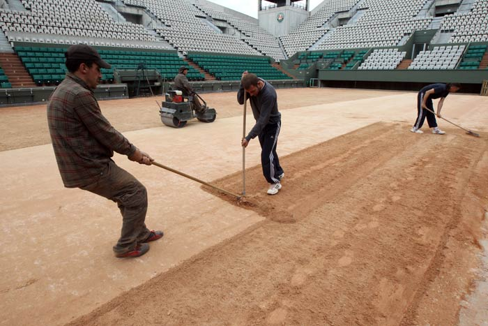 Employees set the last layer of clay on the Suzanne Lenglen court at the Roland Garros tennis stadium in Paris. (AFP Photo)