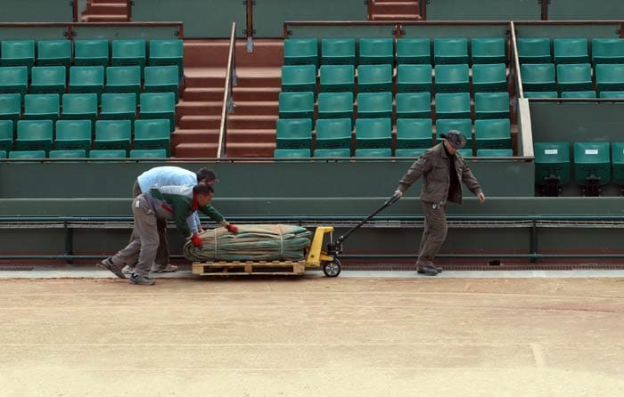 Employees prepare the Philippe Chatrier central court at the Roland Garros tennis stadium in Paris. (AFP Photo)