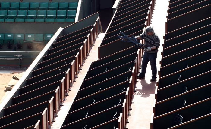 Meanwhile, an employee installs chairs in the bleachers on the Philippe Chatrier central court at the Roland Garros tennis stadium in Paris. (AFP Photo)