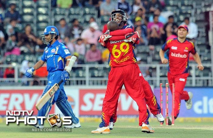 Highveld Lions wicketkeeper Thami Tsolekile congratulates bowler Aaron Phangiso for the wicket of Mumbai Indians' Sachin Tendulkar during Group B Match of the Champions League T20 (CLT20) at the Wanderers Stadium in Johannesburg. (AFP Photo)
