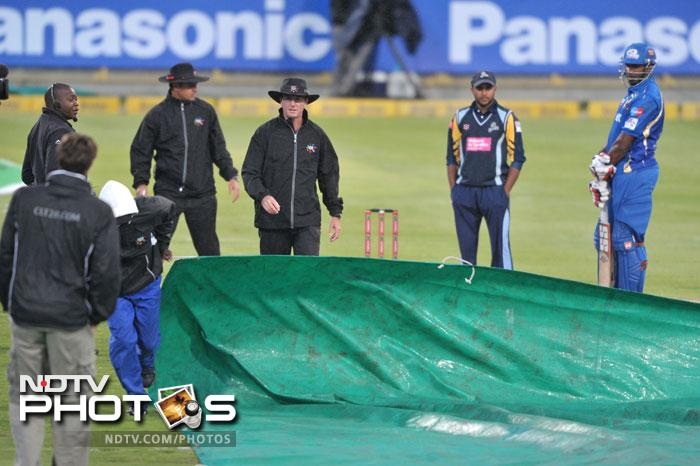 Groundsmen prepare the covers as rain delayed play during Match 11 of the Champions League T20 between the Mumbai Indians (India) and Yorkshire (England) at Newlands Cricket Stadium in Cape Town. (AFP Photo)