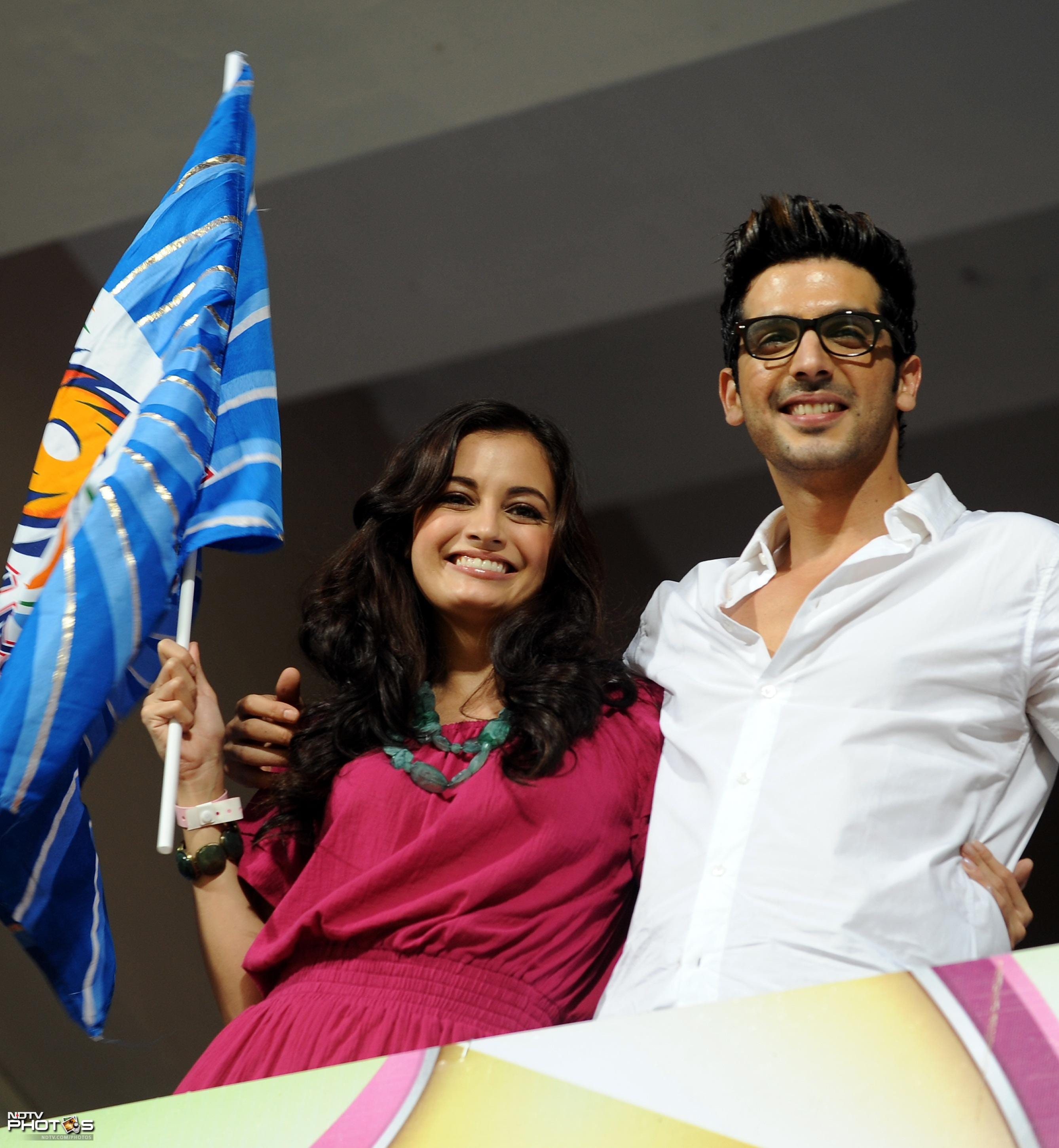 Bollywood actors Zayed Khan and Dia Mirza wave the Mumbai Indians team flags before the start of the Champions League Twenty20 Group A match between Mumbai Indians and Trinidad and Tobago at the M. Chinnaswamy Stadium in Bangalore. (AFP Photo)