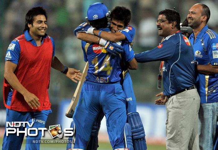 Yuzvendra Chahal is hugged by his teammates after Mumbai Indians won the Champions League Twenty20 League Group A match against Trinidad and Tobago at the M. Chinnaswamy Stadium in Bangalore. Mumbai Indians chased a total of 98 and won the match off the last ball. (AFP Photo)