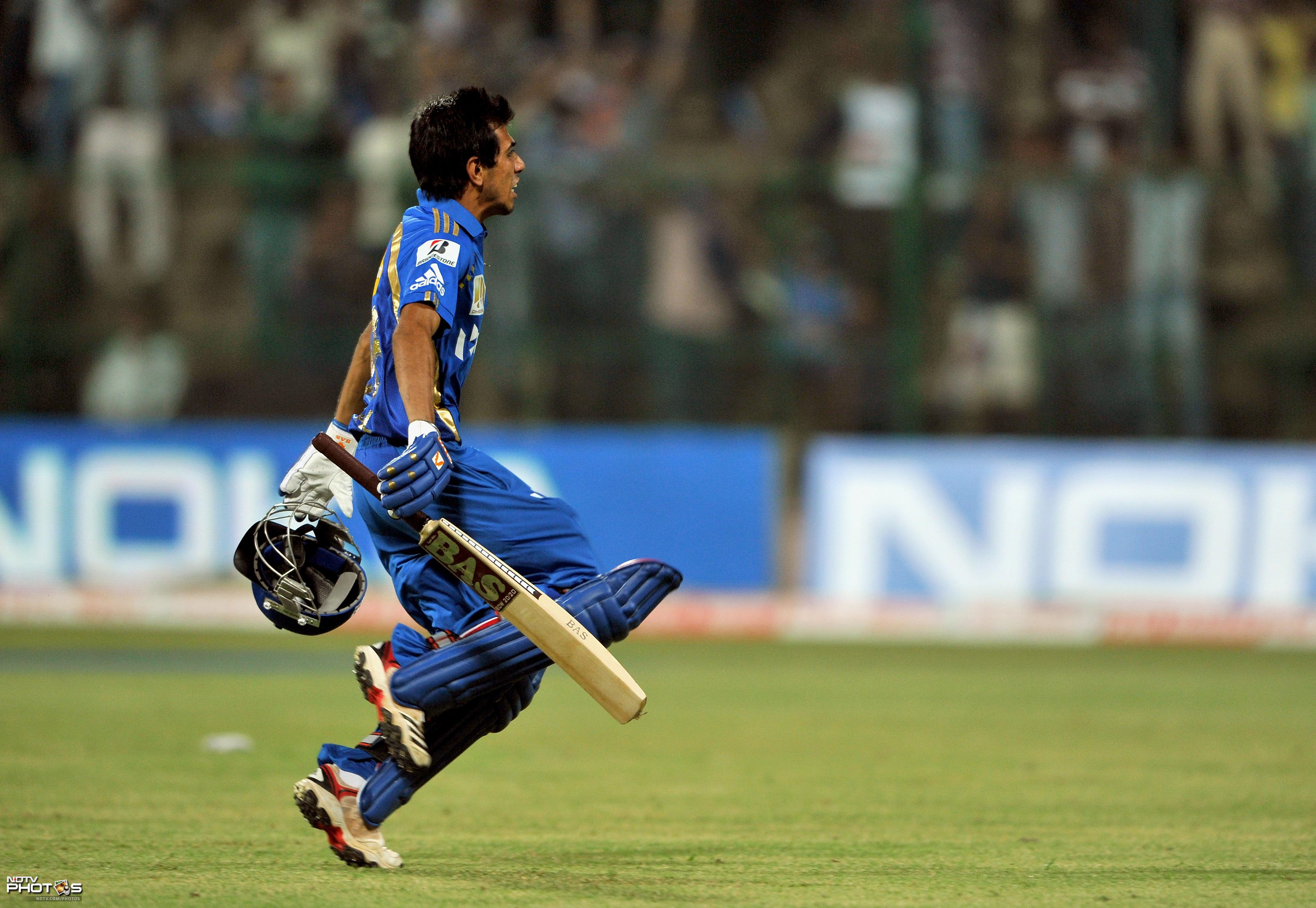 Yuzvendra Chahal runs towards his teammates after scoring winning runs off the last ball during the Champions League Twenty20 League Group A match between Mumbai Indians and Trinidad and Tobago at the M. Chinnaswamy Stadium in Bangalore. (AFP Photo)