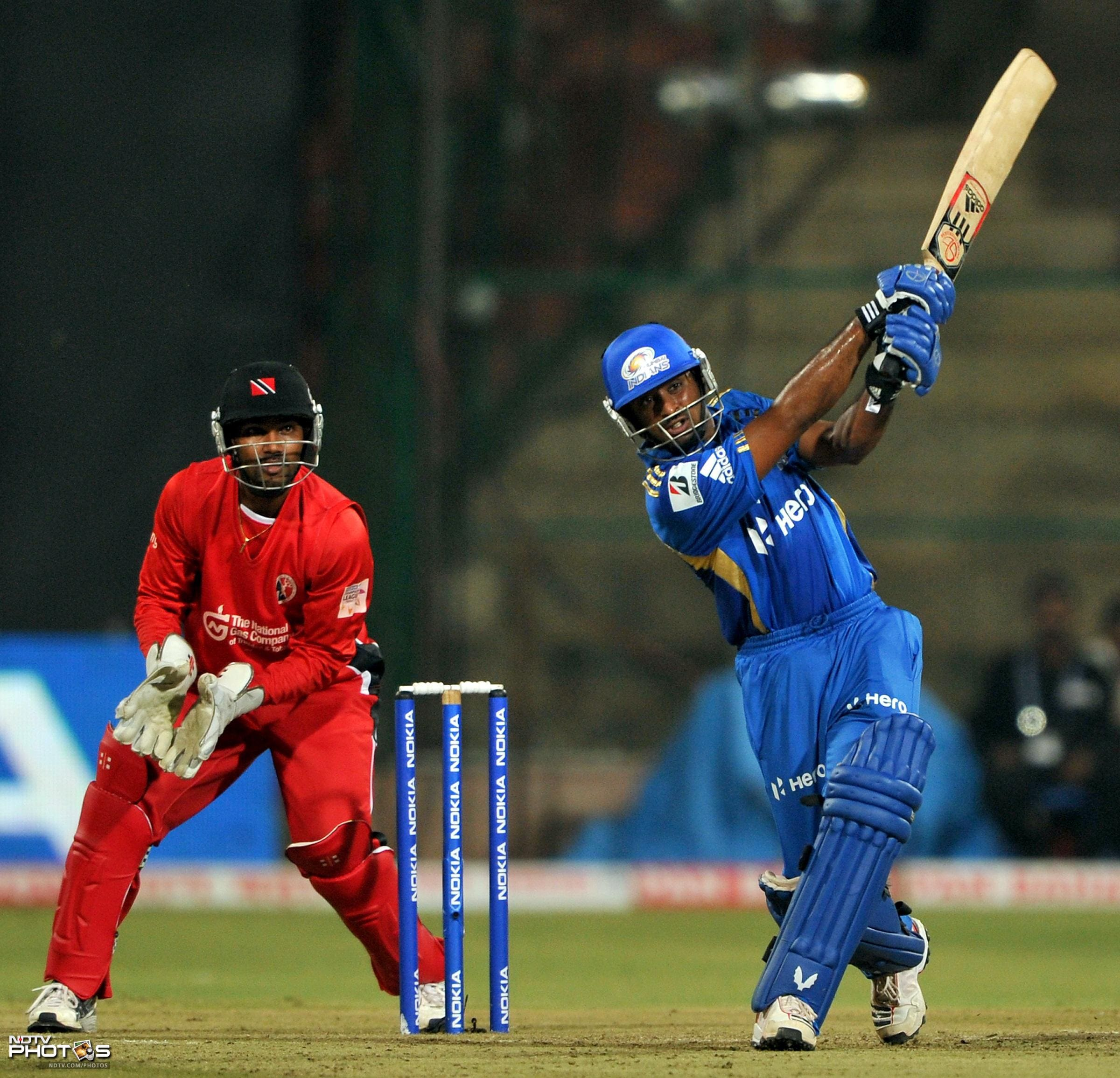 Ambati Rayudu hits a boundary while wicketkeeper Denesh Ramdin looks on during the Champions League Twenty20 League Group A match between Mumbai Indians and Trinidad and Tobago at the M. Chinnaswamy Stadium in Bangalore. (AFP Photo)